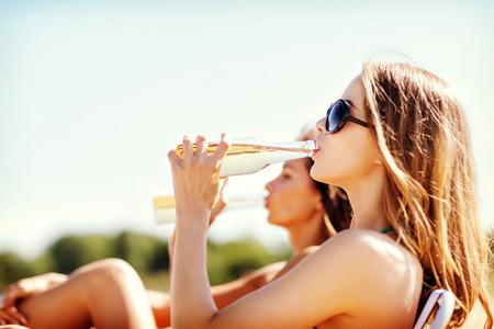 botellas de cerveza: vacaciones de verano y vacaciones - chicas en bikini con bebidas en las sillas de playa Foto de archivo