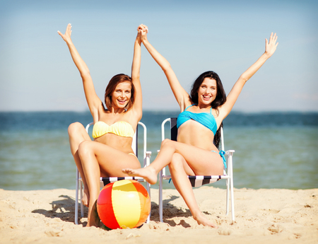 lounges: summer holidays and vacation - girls in bikinis sunbathing on the beach chairs Stock Photo