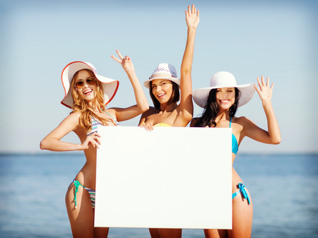 tanned girl: summer holidays and vacation - girls in bikinis holding blank white board on the beach