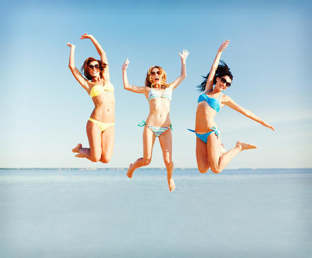 tanned woman: summer holidays and vacation - girls jumping on the beach