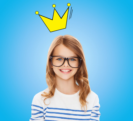 pre teens: education, school, children and vision concept - smiling little girl with black eyeglasses over blue background with crown doodle Stock Photo