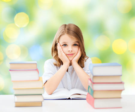 pre teen girls: education, people, children and school concept - little student girl sitting at table with books over green lights background Stock Photo