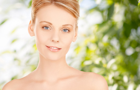 bare women: beauty, people and health concept - beautiful young woman face over green background Stock Photo