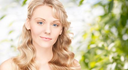 schoonheid, mensen, haarverzorging en gezondheid concept - mooie jonge vrouw gezicht met lang golvend haar op groene achtergrond