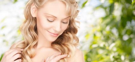 美しさ、人、髪のケアと健康のコンセプト - 緑の背景の上の長いウェーブのかかった髪を持つ美しい若い女性顔