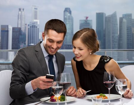 technology, food, holidays and people concept - smiling couple with smartphone eating at restaurant over city background photo