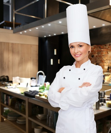 female hand: cooking, bakery, people and food concept - smiling female chef, cook or baker with crossed arms over restaurant kitchen background Stock Photo