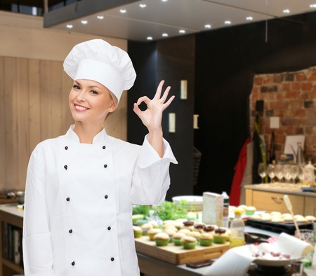 cooking, bakery, gesture and food concept - smiling female chef showing ok hand sign over restaurant kitchen background