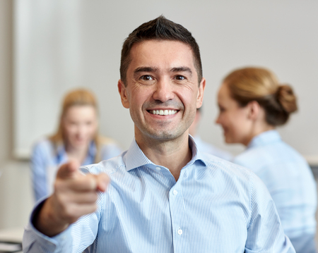 happy businesswoman: business, people, gesture and teamwork concept - smiling businessman pointing finger to you with group of businesspeople meeting in office