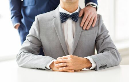 same sex: people, celebration, homosexuality, same-sex marriage and love concept - close up of male gay couple with wedding rings on putting hand on shoulder