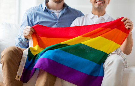 homosexual sex: people, homosexuality, same-sex marriage, gay and love concept - close up of happy male gay couple hugging and holding rainbow flag at home Stock Photo