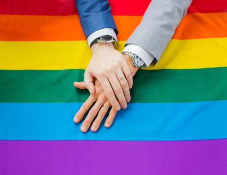 sex: Menschen, Homosexualität, die gleichgeschlechtliche Ehe, Homosexuell und Liebe Konzept - Nahaufnahme von glücklichen männlichen Homosexuell Paar Hände über Regenbogenflagge Lizenzfreie Bilder