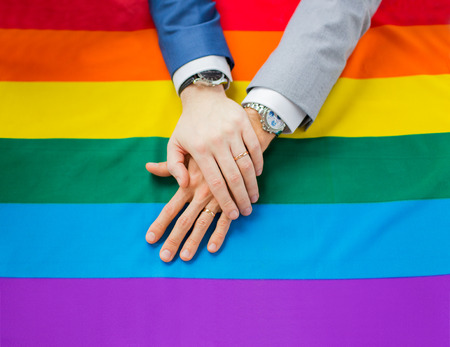 same sex: people, homosexuality, same-sex marriage, gay and love concept - close up of happy male gay couple hands over rainbow flag Stock Photo