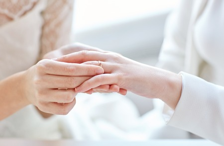 same sex: people, homosexuality, same-sex marriage and love concept - close up of happy lesbian couple hands putting on wedding ring