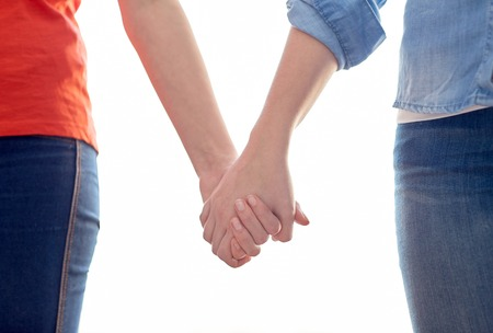 same sex: people, homosexuality, same-sex marriage, gay and love concept - close up of happy lesbian couple holding hands