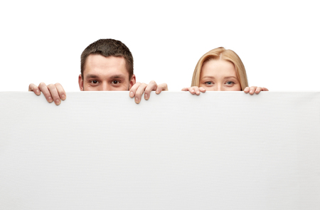 big behind: people, advertisement and information concept - happy couple hiding behind big white blank board Stock Photo