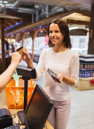 sale, shopping, consumerism and people concept - happy young woman with credit card and wallet buying food at checkout in market photo