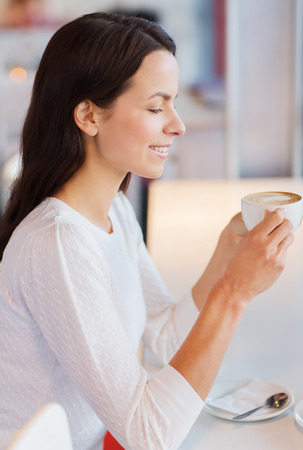 elegant girl: leisure, drinks, people and lifestyle concept - smiling young woman drinking coffee at cafe