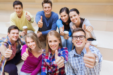 hot girl: education, high school, friendship, drinks and people concept - group of smiling students with paper coffee cups showing thumbs up gesture Stock Photo