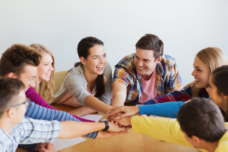 education, teamwork and people concept - smiling students with papers putting hands on top of each other Stock Photo