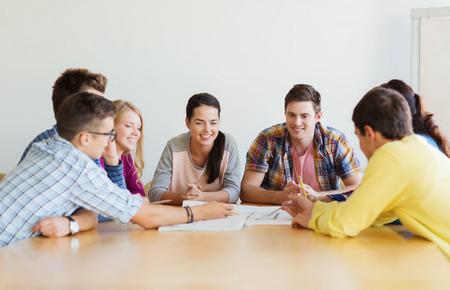 personas trabajando: la educación, la escuela, la arquitectura y el concepto de la gente - grupo de estudiantes sonrientes con reunión anteproyecto interiores