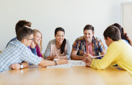 education, school, architecture and people concept - group of smiling students with blueprint meeting indoors Stockfoto