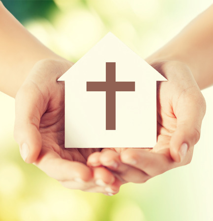 protestant: religion, christianity and charity concept - close up of woman hands holding paper house with christian cross symbol over green background