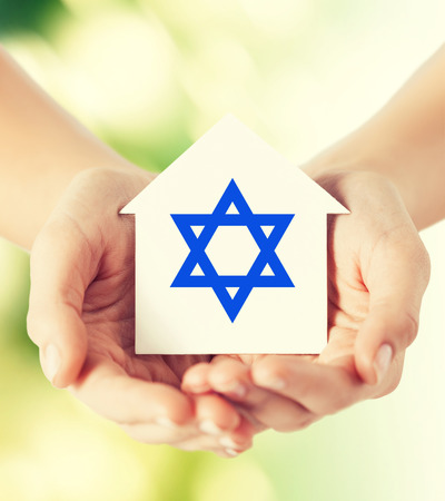 religion, judaism and charity concept - close up of woman hands holding house with star of david over green background Stock Photo
