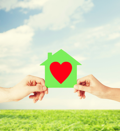 charity, real estate and family home concept - isolated picture of male and female hands holding green paper house with red heart Stock Photo