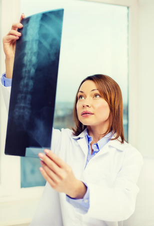 healthcare, medical and radiology concept - concentrated doctor looking at x-ray photo