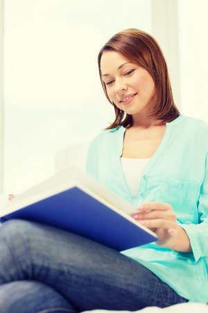 leasure: leasure and home concept - smiling woman reading book and sitting on couch at home
