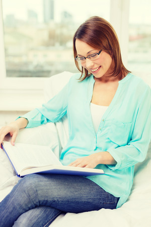leasure: leasure and home concept - smiling woman in eyeglasses reading book and sitting on couch at home Stock Photo