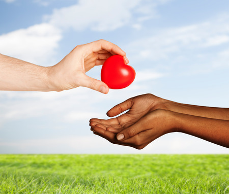 love, charity, valentines day, donation and international concept - close up of man hand giving heart to woman over blue sky and grass background photo