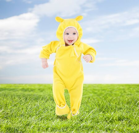 rompers: people, children, achievement and happiness concept - happy baby in yellow suit making first steps over blue sky and grass background
