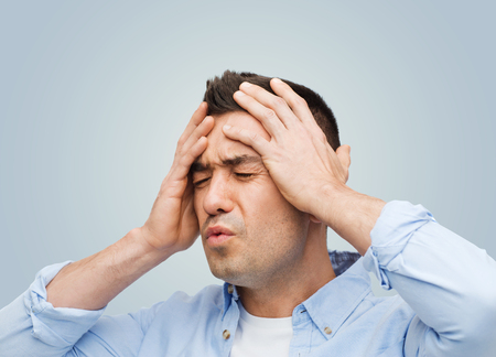 stress: stress, headache, health care and people concept - unhappy man with closed eyes touching his forehead over gray background