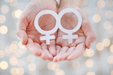 nude lesbian: people, homosexuality, same-sex marriage, gay pride and love concept - close up of happy lesbian couple hands holding white paper venus symbol over holiday lights background