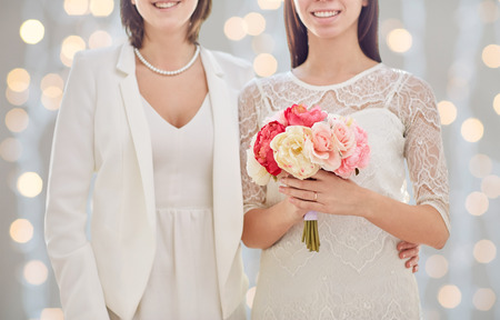 people, homosexuality, same-sex marriage and love concept - close up of happy married lesbian couple with flower bunch over holiday lights background