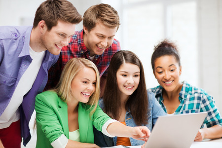 chat group: education concept - smiling students looking at laptop at school