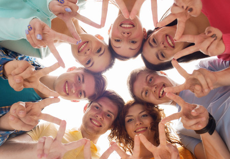 friendship, youth, gesture and people - group of smiling teenagers in circle showing victory sign Stock Photo