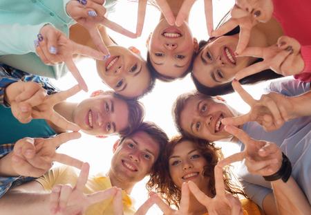 muchas personas: la amistad, la juventud, el gesto y la gente - grupo de adolescentes sonrientes en círculo que muestra signo de la victoria