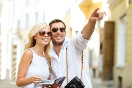 travel: summer holidays, dating, city break and tourism concept - couple with camera and travellers guide