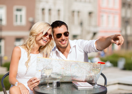 romantic couple: summer holidays, dating and tourism concept - couple with map in cafe in the city Stock Photo