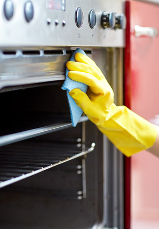 people, housework and housekeeping concept - close up of woman hand in protective glove with rag cleaning oven at home kitchen Reklamní fotografie - 38879382