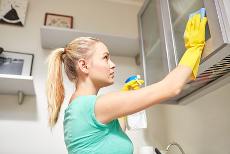 cleanser: people, housework and housekeeping concept - happy woman cleaning cabinet with rag and cleanser at home kitchen