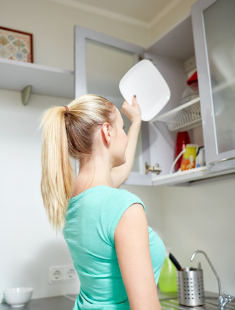 people, housework and housekeeping concept - happy woman putting plate to kitchen cabinet Banco de Imagens