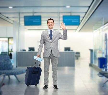 personas saludando: viaje de negocios, viajes, equipaje y concepto de la gente - hombre de negocios feliz en juego con la bolsa de viaje y la entrada de aire agitando la mano sobre fondo aeropuerto Foto de archivo