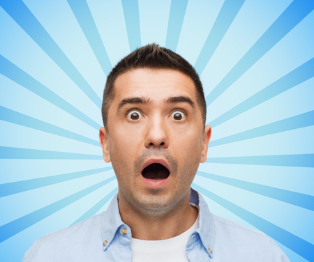 fear face: fear, emotions, horror and people concept - face of scared man shouting blue burst rays background