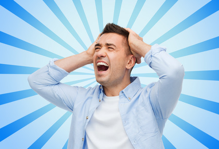 stress, headache, health care and people concept - unhappy man with closed eyes touching his head blue burst rays background Stock Photo