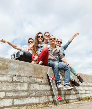 zomervakantie en tiener concept - groep van lachende tieners met boob doos en Skatboard opknoping buiten