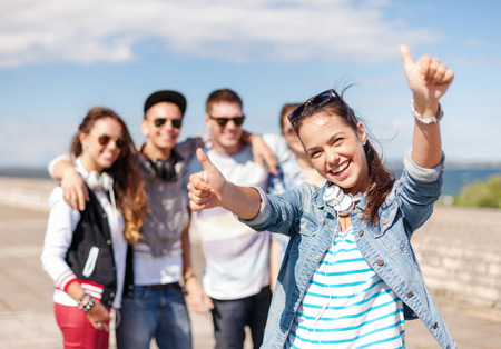 summer holidays and teenage concept - teenage girl in sunglasses and headphones hanging out with friends outside and showing thumbs up